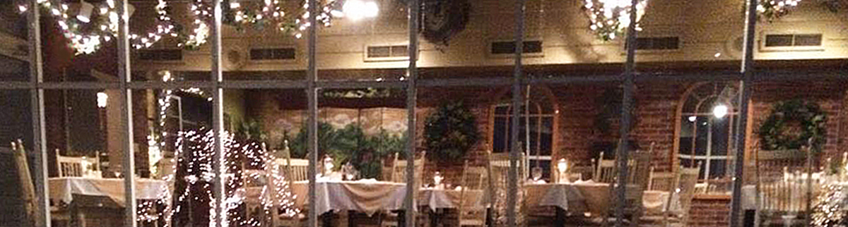 view through windows into restaurant dining room with 6 tables, white tablecloths, chairs, red brick wall, twinkling lights