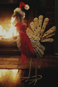 turkey sculpture standing beside blazing fireplace wearing red & white Santa hat & red ribbon around neck