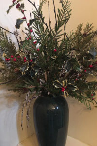 black vase filled with evergreens and holly with red berries