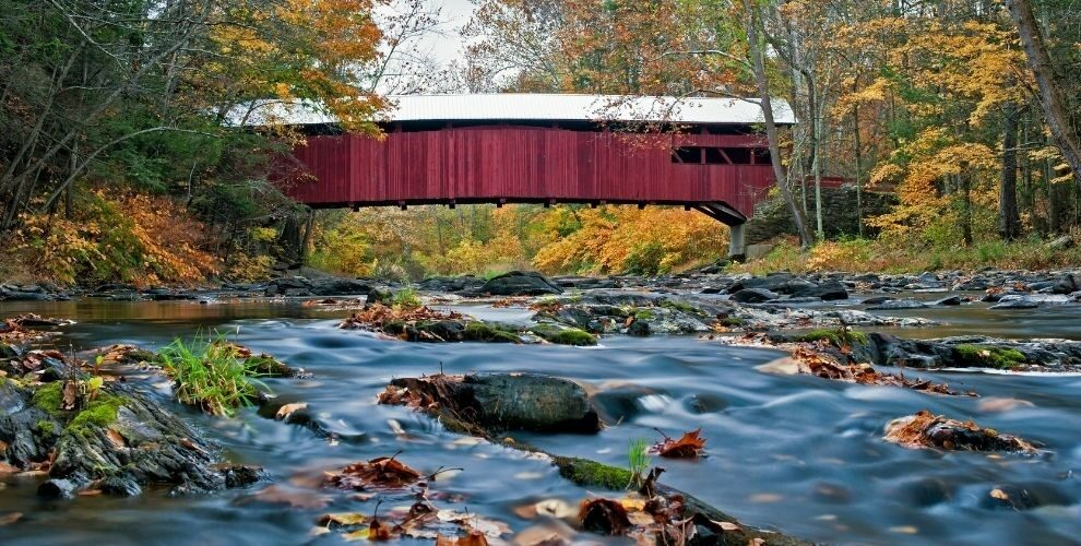 Covered bridge spanning a river with fall trees on either side.