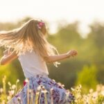Little blonde girl spinning in a field in sunshine