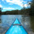 bow of turquoise kayak heading up quiet river shoreline trees & blue sky with white clouds reflected in water