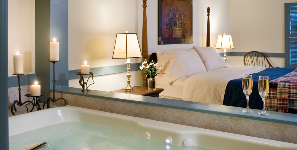 whirlpool tub filled, 4 candles lit and two glasses of wine on the edge in clear view of king size bed in room