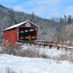 Kramer covered bridge with red vertical siding surrounded by snowy landscape