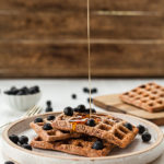 Thin stream of pouring from above on waffles with blueberries on top small white bowl of blueberries & waffle on board