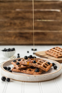 Maple syrup pouring on waffles with blueberries Photo by Lindsay Moe on UnSplash