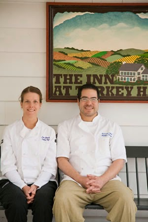 female and male chefs wearing white chef jackets sitting on bench in front of clapboard wall with Inn at Turkey Hill graphic sign