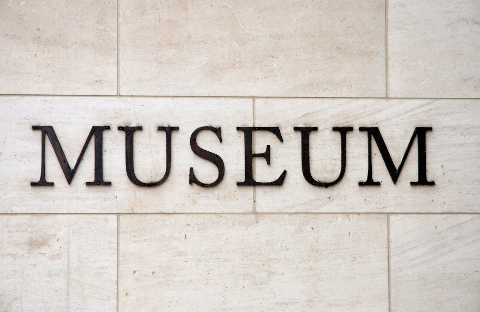 white brick wall with black letters of sign says MUSEUM