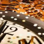 quadrant of clock with hands approaching midnight surrounded by confetti and gold ribbons