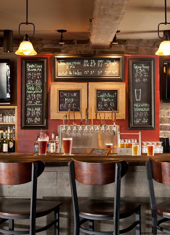 view of bar front at the Brewpub with bar chairs set at bar and chalkboard signs in background with tap of several beers