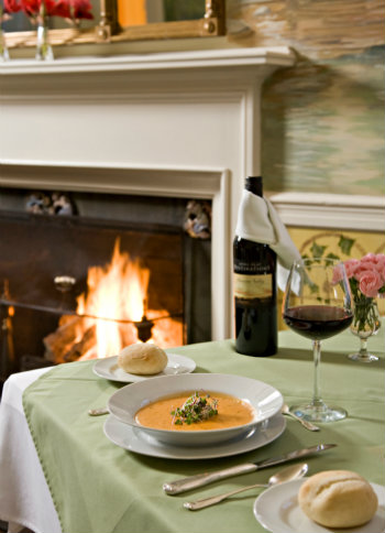 indoor dining table set for one set along fireplace, displaying delicious bowl of soup with a side of bread and wine to compliment the meal