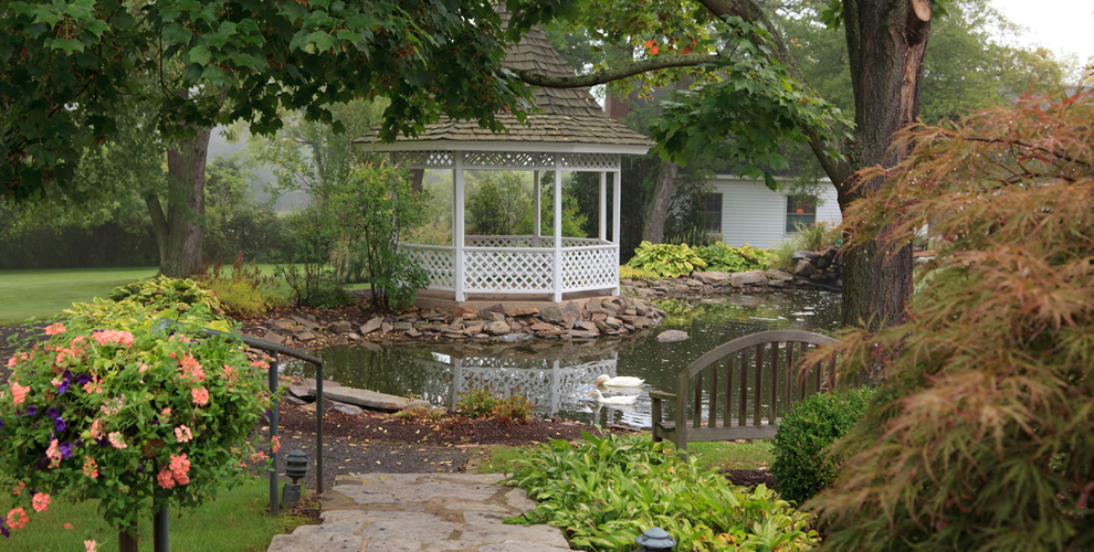 view of pond and white gazebo surrounding by benches and overhead tree making a beautiful courtyard area for guests