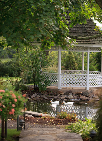 far view of white gazebo next to pond