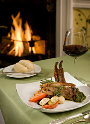 meat, vegetables on white square plate, rolls, knife on small plate, glass of red wine, on sage tablecloth, blazing fireplace