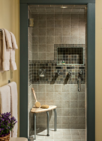 gray tiled shower stall with small white bench, white towels on 2 towel bars on yellow wall to left