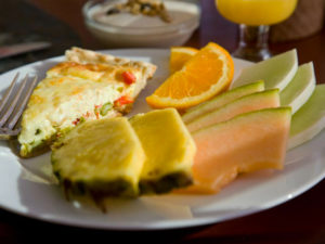 breakfast quiche on white plate with orange & pineapple slices