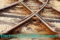 closeup of two intersecting sets of rails on brown railroad ties with lighter gravel between ties Aqua Text: Electric City Trolley Museum