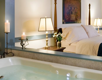 whirl pool tub filled with lit candles on side with view of king size bed