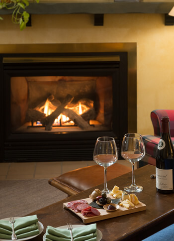 two wine glasses with board of cheese and fruit array set on coffee table in front of fireplace