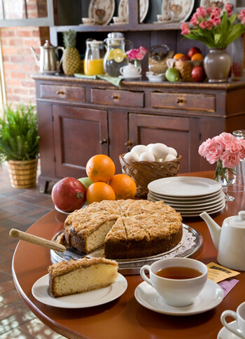 table with white china pot, cup of coffee, piece of cake cut from round cake, oranges apple, plates, pink carnations