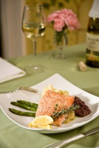Square white plate with pink salmon filetand asparagus stalks and glass of white wine and wine bottle behind plate