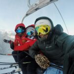 Three skiers covered in winter gear sit on a chair lift.