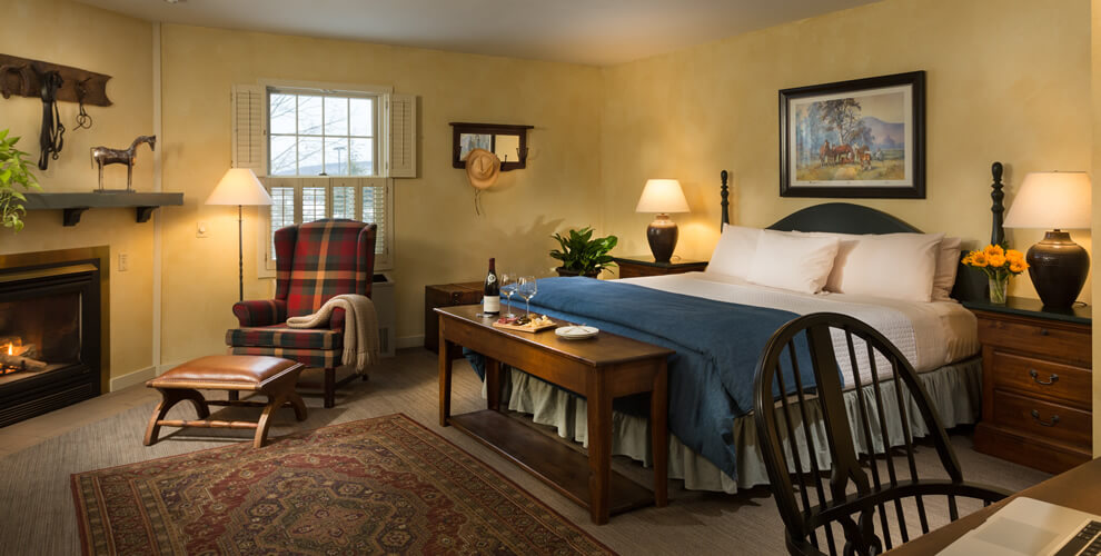 Inn room with fireplace wingchair king bed with blue & white bedding chair desk