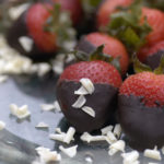 5 chocolate dipped strawberries on glass plate with white chocolate shavings scattered over them