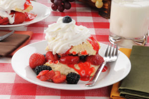 strawberry & blackberry shortcake topped with whipped cream and blueberry on white plate with fork red & white check tablecloth