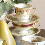stack of three decorated fine china tea cups and saucers with gold napkin on left and white flowers in background