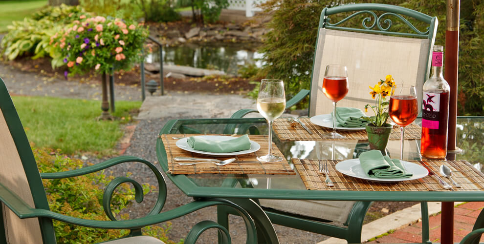 outdoor table display of green farmhouse tables with glass table top, set for 3 guests with fresh wine by the bottle poured for each glass