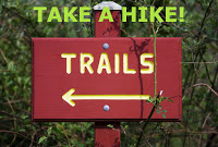 red painted wooden sign directing left for hikers to arrive at Trails
