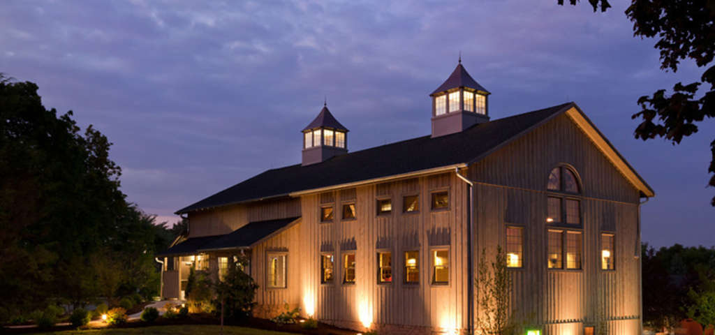 facade of turkey hill brewing company pole barn - brown vertical siding with two lighted cupulas