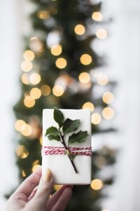 hand holding white gift box with holly sprig in front of blurry christmas tree with white lights